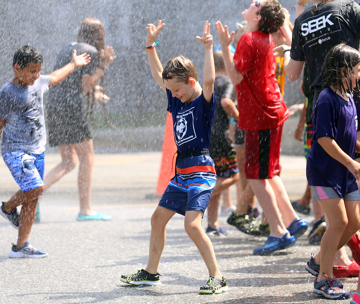 HOLLY PELCZYNSKI - BENNINGTON BANNER 5th grader Jessie Nesbit dances in the rain of a fire hose during Totus tuus camp at Sacred Heart St. Francis De Sales church in Bennington on Friday afternoon during their water day celebration, held in Bennington.