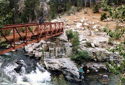 Trail bridge on San Joaquin River, fly fisherman along river below.