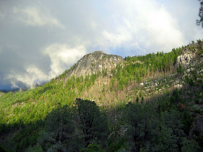 Back at the trailhead backpacker's camp, the clouds are starting to break. Sunshine lights up a nearby peak.