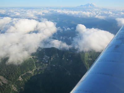 There were clouds in the sky, but we could easily see the ground between them.  Here we are flying over Snoqualmie Pass.