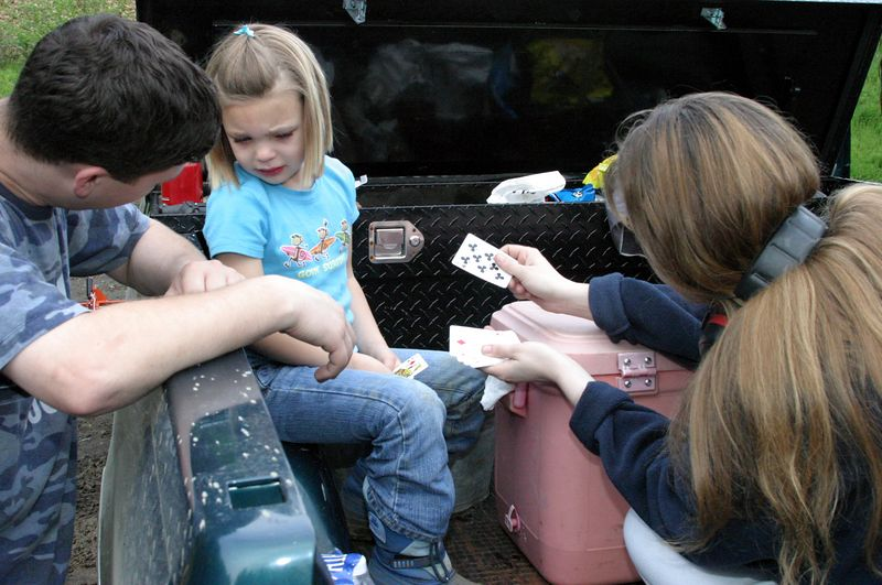 """<font size=""""+1"""">Okay, back to the saga of Hailey's eye..  We're near the end of the day and Hailey is REALLY starting to be unhappy.  Sarah is trying hard to distract the children with a game of cards while the rest of us play with firearms, but the ploy is starting to wear thin.. </font>"""