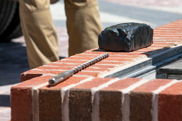 The bronze brick is installed to the base of the George Mason statue at the Enslaved People of George Mason Memorial in Wilkins Plaza. Photo by: Shelby Burgess/Strategic Communications/George Mason University