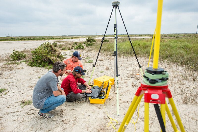 Conrad Blucher Institute for Surveying & Science researchers Jake Berryhill (left), Alistair Lord, and Brian Lorentson (back) collect data at the Mustang Island marshes following Hurricane Harvey.