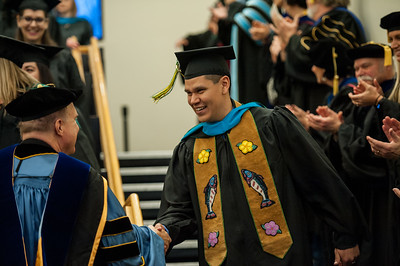 Walter W. Kookesh, Master of Public Administration, is congratulated by faculty after UAA's Fall 2017 Graduate Degree Hooding Ceremony.  171216-HOODING-JRE-0811.jpg