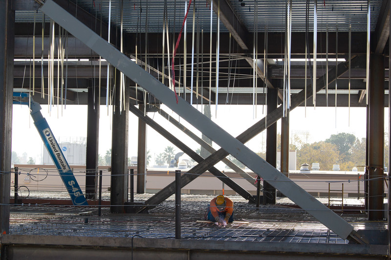 A construction worker welds the flooring on the Science and Engineering building.