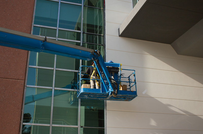 Construction workers put the finishing touches on the windows in the Campus Center breezeway.