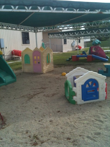 the outdoor sand pit area of the Child Development Center has a few small playhouses that children can hang out in.