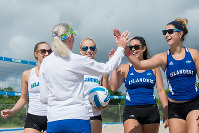 Islanders sand volleyball team high five Mrs. Killebrew following the first ceremonial serve during the grand opening of Sand Volleyball courts.