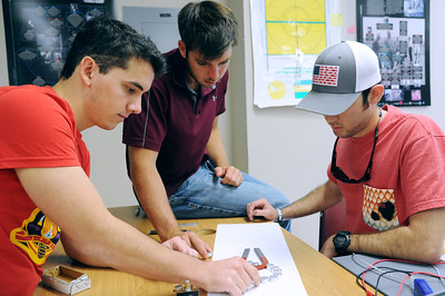 Students Juan De Vere(left), Tanner Geiser and Andres Rodriguez use a compasses to determine the magnetic field of a horizontal horseshoe magnet.