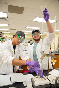 Students Brent Schultz and Eli Alvarez work together on titrating NaOH with HCl in General Chemistry II.