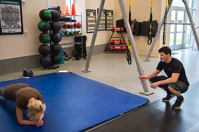 Personal trainer Cody Lang assists a student in the Dugan Wellness Center.