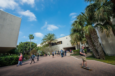 Students make their way between buildings on a beautiful day on campus.