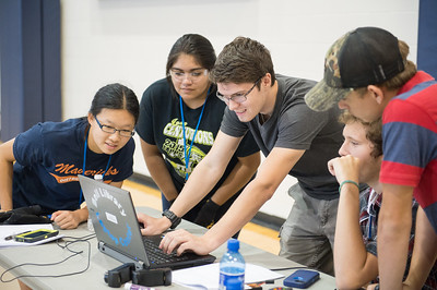 Student Alex Harrison (center) assists his team with mapping their Unmanned Air System to a controller in 2015 UAS Summer Institute.