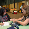 Nursing Student Dana Matthews(right) records blood pressure, BMI and blood sugar screenings of Student Rachel Rambo during Student Nurses Association Health Fair event