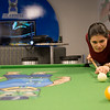 Danielle Garcia takes a break to play pool with friends in the UC's break room.