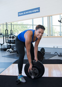 Kaelin Simmons changes to a different weight after one session of hang snatch in her Weight Training class in the Dugan Wellness Center.