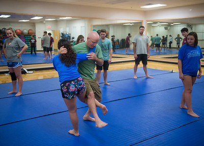 Professor Paul Bystedt is taken down by one of his students during a demonstration in Self Defense class.