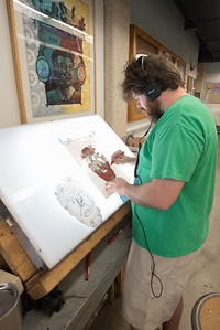 Ross turner works on his art piece in the center for arts.