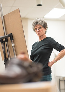 Student Phyllis Finley concentrates on measuring objects from a still life during Drawing I.