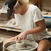 Marley Dickert patiently throws a clay bowl on the electric wheel in Ceramics I.
