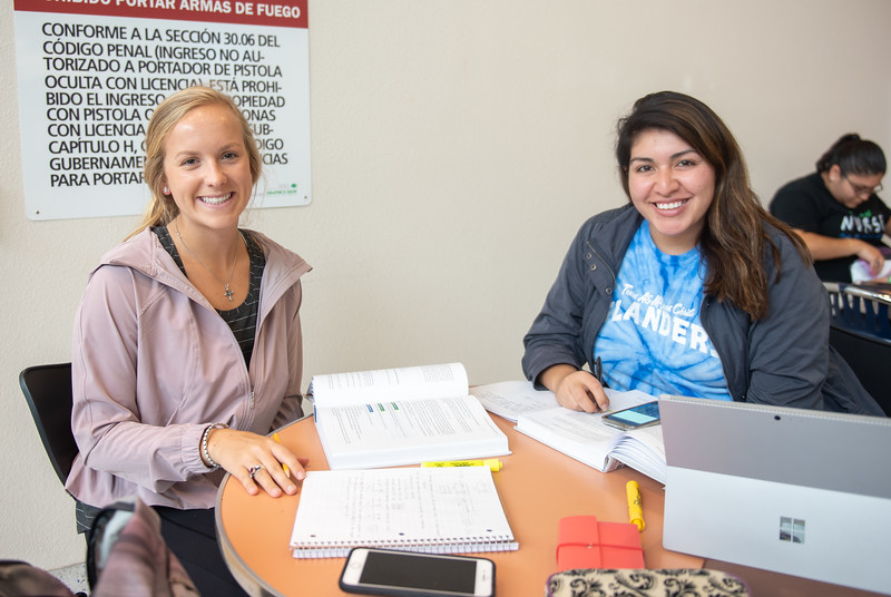 Cassidy Zajicek (left) and Erica Rios work on their Measurement and Evaluation assignment on the first floor of Islander Hall before their next class.