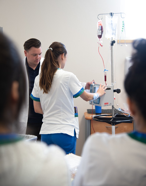 Simulation Lab Coordinator Brayton Amidon (left) leads the OB Rotation Simulation as he demonstrates how to complete a blood transfusion in the University's Islander Hall mock hospital.