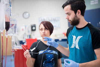 Clinical assistant professor Eloisa Beltran assists student Grant Lunstent with his IV check-off for preoperative clinical day.