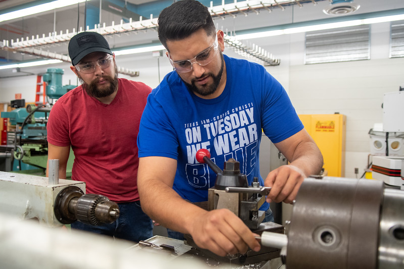 Brandon Hayatt (right) goes over machining a shaft for a lab project with Jeremy Martinez that will be used in various manufacturing processes.