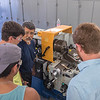 """""""Lab Coordinator Jack Esparza teaches students (left to right) Jerry Shea, Luke Condron, and Dante Leal how to operate a Lathe."""