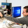 Student Andrew Garcia adjusts the Oscilloscope during a lab session for Digital Systems.
