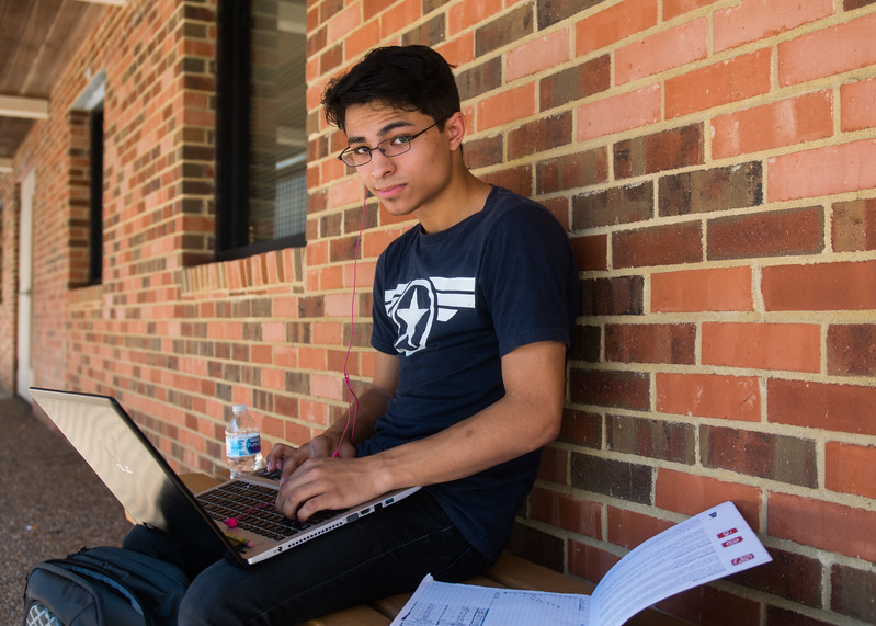 Student Michael Williams studies for his Chemistry exercises behind the Glasscock Student Success Building.