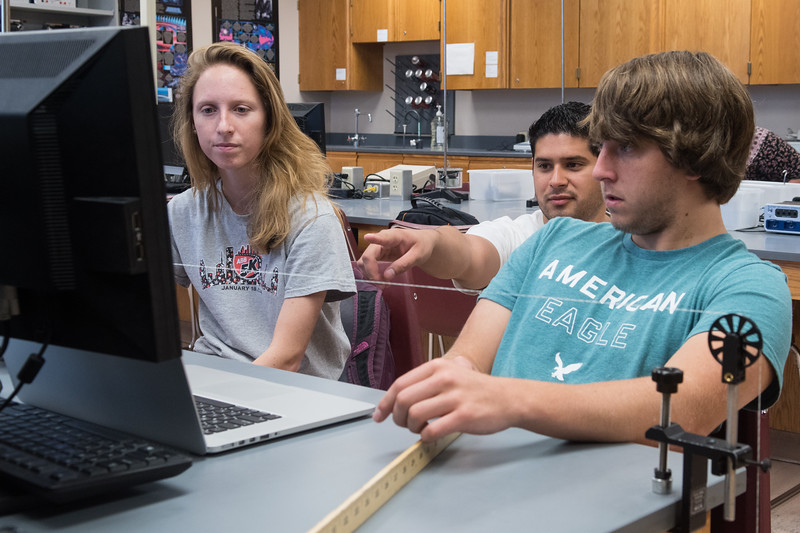 Camille Felgenhaver (left), Luis Hernandez, and Noah Johnson work on a experiment in University Physics II.