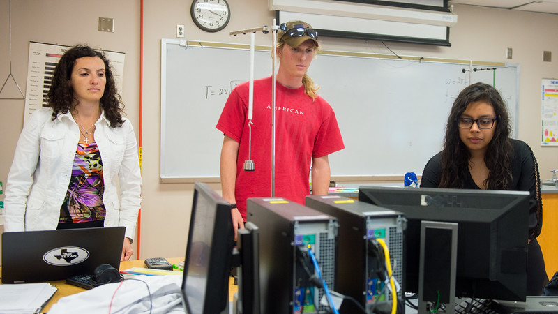Students Daina Marales (left), James Trottes, and Elsy Hernandes use a computer to measure and compare data they gather during Physics II.