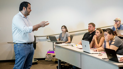 Dr. Oliver Cruz-Milan answers a student's question during his Advertising and Promotional Strategy class.