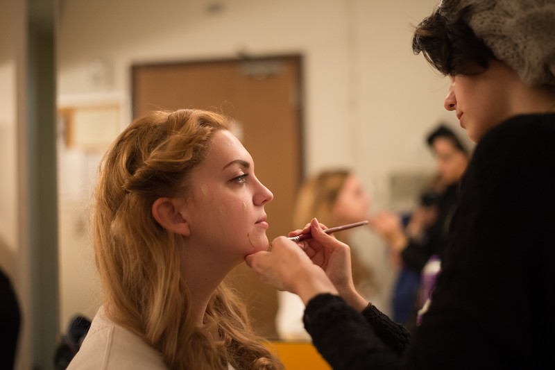 One student applies another's makeup before rehearsals.