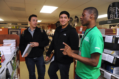 Student worker Devin Farrel(Right)l assists students Zachary Antooko and Chris Gutierrez finding their textbooks.