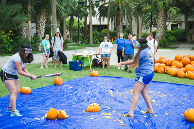 TAMUCC Students Jessica Mendez(left) and Lauren Lopez(right) de-stress by smashing pumpkins in the Center of Instruction Plaza.