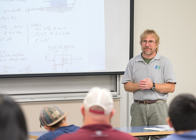 Assistant Professor Dr. Andrew Conkey reviews problems with his students during his Dynamics course.