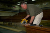 Terry Corey cuts sections of the players bench to give to alumni athletes.