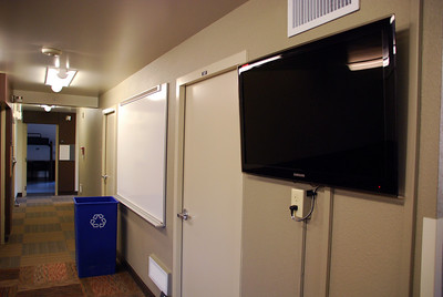 """LCD TV's were added to LLC's for educational and community purposes. Recycling bins are now located in more central areas and dim """"porch lights"""" were inserted beside each room, allowing the main lights to take a break every evening to save energy. In addition, community dry erase boards decrease the need for paper banners as do individual boards beside each door. Taken by Sarah White '11."""