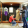 WELL-DRESSED: Fashion merchandising students meticulously dress the new display cases in the first floor entryway.