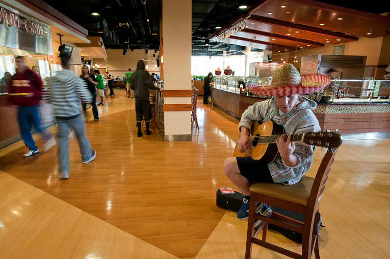 A GMU student wearing a sombrero plays a guitar in the Southside dining facility at the Fairfax Campus during Hispanic Heritage Month.