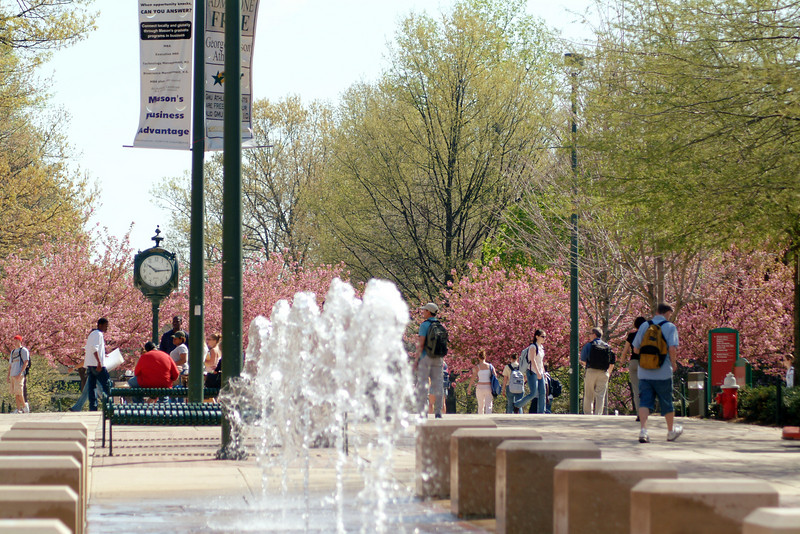 North Plaza fountain and the clock with cherry blossom trees in bloom. Photo by Creative Services/George Mason University. 040419052