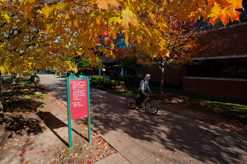 A student rides a bike by the Science and Tech 1 building at Fairfax Campus.