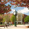 Clock with students walking by on the North Plaza of the Fairfax Campus in the spring. Photo by Creative Services/George Mason University 050427166