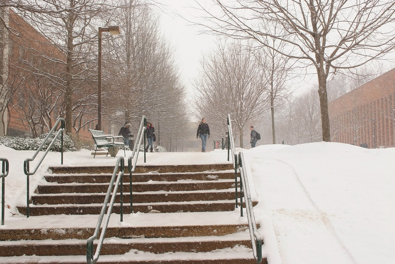 Students walk on campus in the snow.  Photo by Creative Services/George Mason University