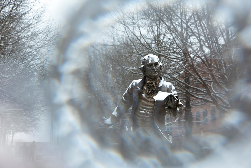 Snow falling on the George Mason statue at Fairfax campus. Photo by Bethany Camp/Creative Services/George Mason University