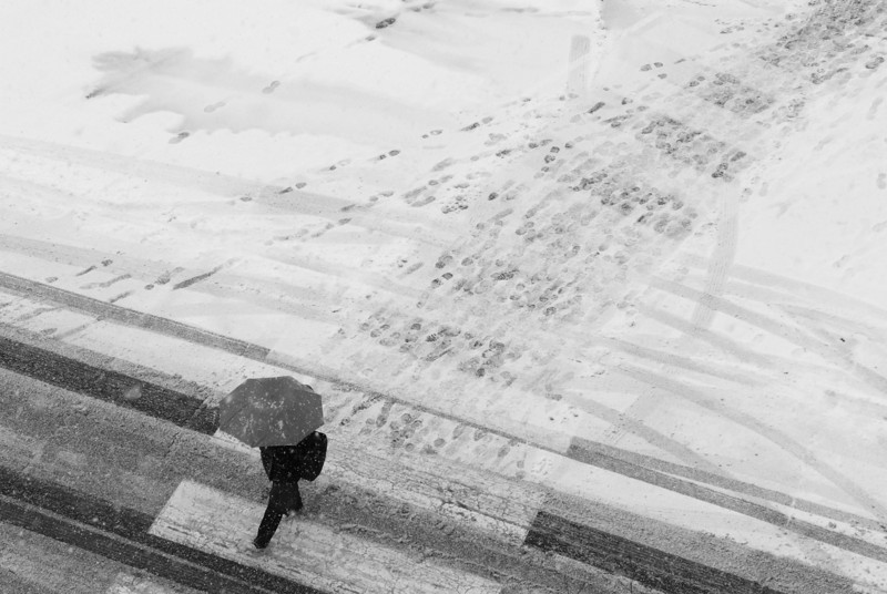 B&W.  A student walks across an empty street on campus in the snow.  Photo by Evan Cantwell/Creative Services/George Mason University