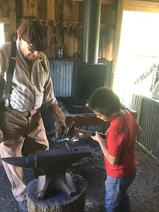 Andrew Juarez is taught the trade of blacksmith while visiting Heritage Village.