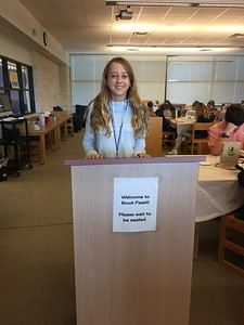 Emily Porter, library aide, seating students as the hostess of Book Feast